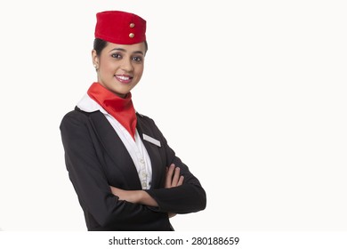 Portrait of young air hostess with arms crossed standing against white background