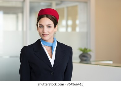 Portrait of young air hostess standing at airport and looking at camera. Portrait of flight assistant in uniform standing near check in counter. Happy agent wearing the hostess uniform at airport.