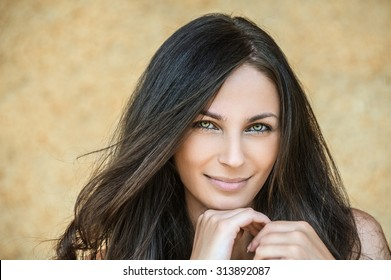 Portrait of young alluring smiling attractive brunnete woman propping up her face against yellow background.