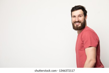 Portrait of young amazed bearded man isolated on gray background