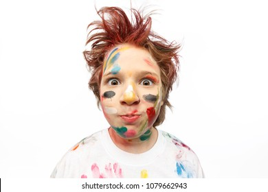 Portrait of young amazed boy, his face and hands painted with paints, vivid emotions, messy hair