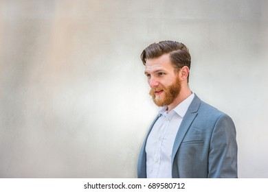 Portrait of Young American Hipster Businessman with full beard on silver metal background.
