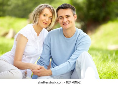 Portrait of young amorous couple looking at camera in park
