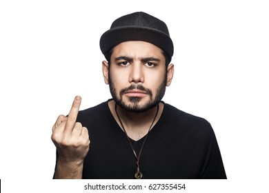 Portrait of young angry man with black t-shirt and cap looking at camera and showing middle finger. studio shot, isolated on white background.