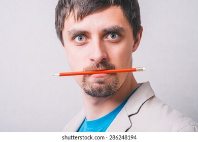 Portrait of a young angry man with pencil. Isolated on white.