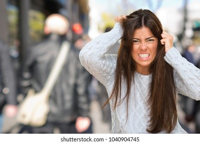 Portrait Of A Young Angry Woman against a street background