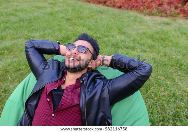 Portrait of Young Arab Masculine Man Student, Which Lies on Soft Green Chair, Dreams, Meditate, Thinking About Something, Smiling and Looking at Heaven, Hands Behind Head on Background of Green Grass