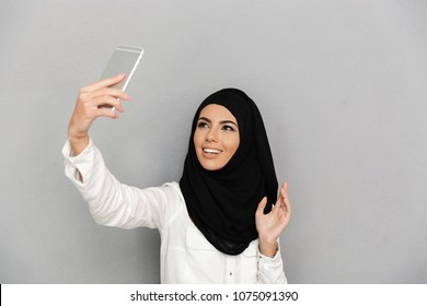 Portrait of young arab woman 20s in islamic headscarf with oriental makeup taking selfie on silver smartphone isolated over gray background