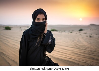 Portrait of a young Arab woman wearing traditional black clothing during beautiful sunset over the desert.