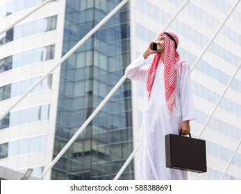 Portrait young arabian businessman holding bag and talking on the phone in the modern city, feeling smart, happy and successful concept