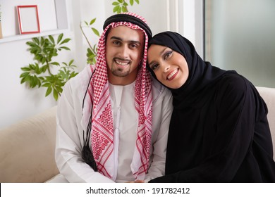 Portrait Of Young Arabic Couple Sitting On Sofa