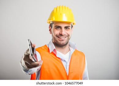 Portrait of young architect handing telephone like taking call on gray background