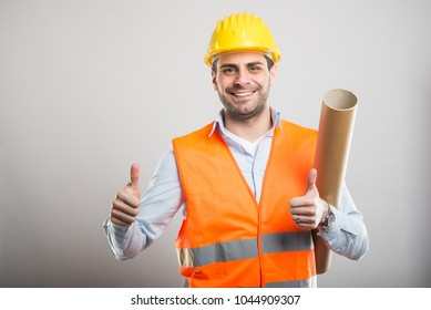 Portrait of young architect holding blueprints showing double like gesture and smiling on gray background with copyspace advertising area