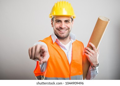 Portrait of young architect holding blueprints pointing camera and smiling on gray background