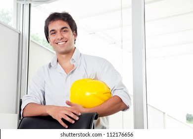 Portrait of young architect holding hard hat in office.