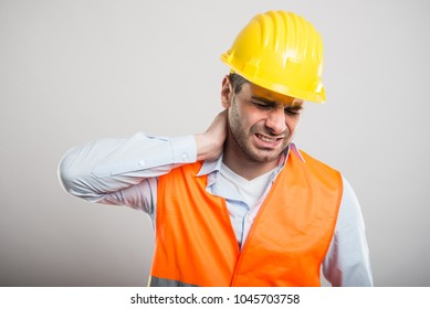 Portrait of young architect holding neck like in pain on gray background