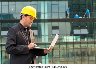 Portrait of young architect using laptop against building background