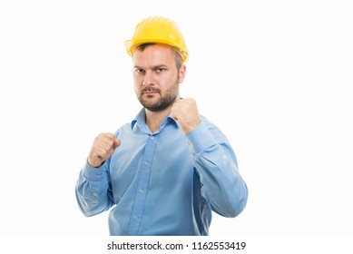 Portrait of young architect with yellow helmet showing both fists gesture isolated on white background with copyspace advertising area