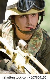 Portrait of young armed Ukrainian soldier.National guard solider talking on radio headset.Dangerous military man with gun.Armed forces with automatic rifle weapon.Border patrol soldier with rifle fun