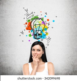 A portrait of a young artful brunette lady who is trying to create a new idea for some business project or case study. A colourful lightbulb as a concept of a new idea is drawn on the concrete wall.