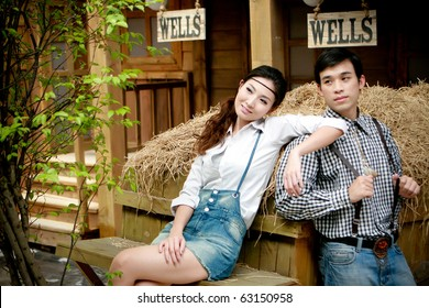 Portrait of young artistic couple in romantic emotion standing beside thatch