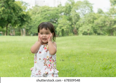 Portrait of young Asia girl playing in green outdoor park happily