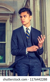 Portrait of Young Asian American Businessman in New York City, wearing black three pieces suit, patterned necktie, vest, hand touching cuff of sleeve, standing by railing inside old office building.