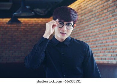 A portrait of Young asian Attractive man working on a tablet.  Business man holding a glassed in hand, select focus use effect filter. Vintage style with concept young new business man.