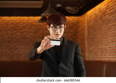 A portrait of Young asian Attractive man working on a tablet.  Business man holding a credit card in hand, use effect filter. Vintage style with concept young new business man.