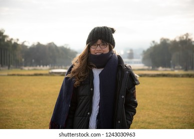 A portrait of a young Asian Australian woman standing in front of the Old Parliament House  and Mt Ainslie in the early morning in winter, Canberra, Australia.