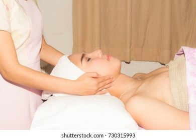 Portrait of Young Asian Beautiful Woman Beauty Face Relaxing with Hand Massage by Spa Therapist.