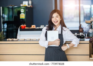 Portrait of Young asian beautiful woman barista in her shop. Cafe restaurant service,