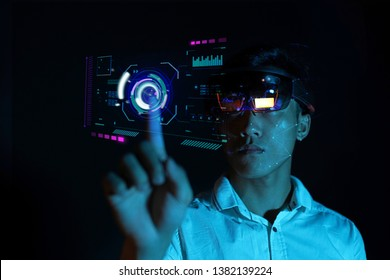 Portrait of young Asian boy experiencing augmented reality and virtual reality communication with hololens glasses