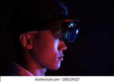 Portrait of young Asian boy experiencing augmented reality and virtual reality communication with hololens 1 glasses