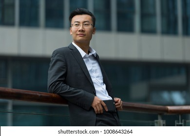 portrait of young asian buisnessman in front of office building