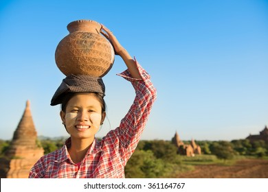 Portrait of Young Asian Burmese traditional female farmer carrying clay pot on head, Bagan, Myanmar