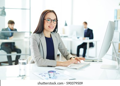 Portrait of young asian business analyst typing at modern computer sitting at her workplace in light office with statistics document beside her