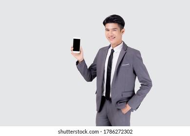 Portrait jung asiatischer Geschäftsmann zeigt und präsentiert Smartphone mit Erfolg einzeln auf weißem Hintergrund, Geschäftsmann steht und hält Telefon, Kommunikationskonzept.