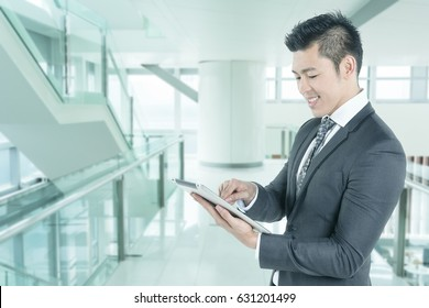 Portrait of young asian business man wear grey suit hold digital tablet in hand and look smile on his face in modern office with copy space area