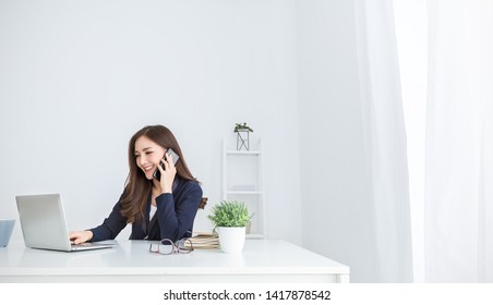 Portrait of young asian business woman talk on smartphone write in notebook with laptop in office. Beautiful girl at desk computer take order, Startup businesswoman online telemarketing sme concept