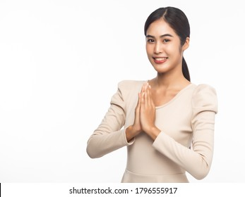 Portrait of young asian business woman greeting with Thai culture Sawasdee, welcome expression isolated on white background.