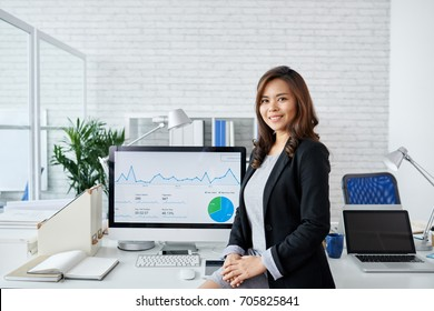 Portrait of young Asian business woman standing at computer with financial chart on it