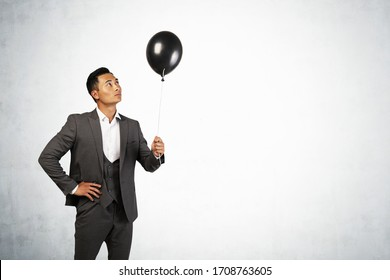 Portrait of young Asian businessman in elegant suit holding black balloon standing near concrete wall. Concept of dream and opportunity. Mock up