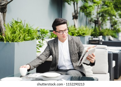 Portrait of a young asian businessman in grey suit reading newspaper with cup of coffee while sitting at rooftop restaurant,smoking area zone.