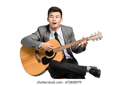 Portrait of a young asian businessman with guitar. Isolated on white background with clipping path