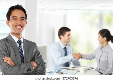 A portrait of a young asian businessman, with his team behind shaking hand