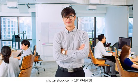 Portrait of young Asian businessman, manager or business owner, arms crossed and smile, with colleague coworker working in office. Corporate business, young entrepreneur, or leadership concept