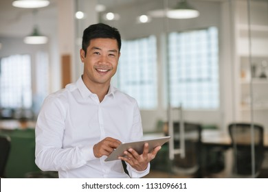 Portrait of a young Asian businessman smiling while standing alone in a large modern office working online with a digital tablet