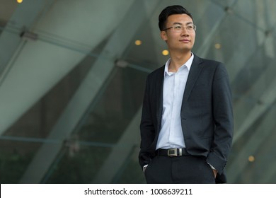 portrait of young asian businessman standing infront of office building