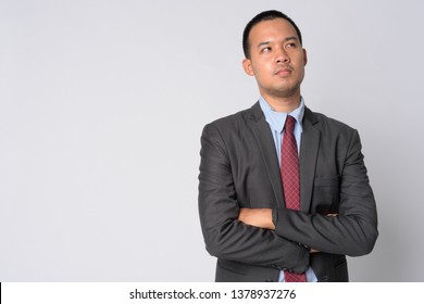 Portrait of young Asian businessman thinking with arms crossed